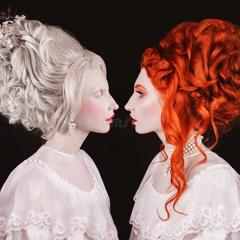 Two renaissance queen with hairstyle in white dress. Face profile. Beautiful victorian woman portrait. Renaissance halloween look. Redhead and blonde princess royalty free stock photography