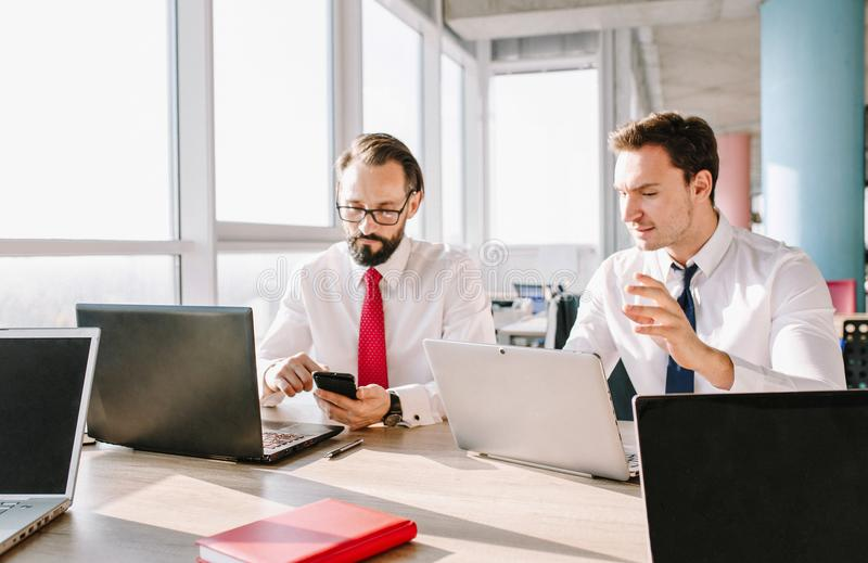 Startup diversity teamwork. Two representative coworkers in office. sitting at desk and working with laptop and smartphone royalty free stock image
