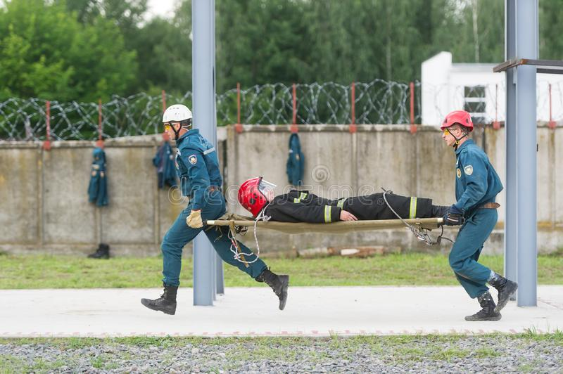 Two rescuers move the injured person on a stretcher for first aid. stock photography