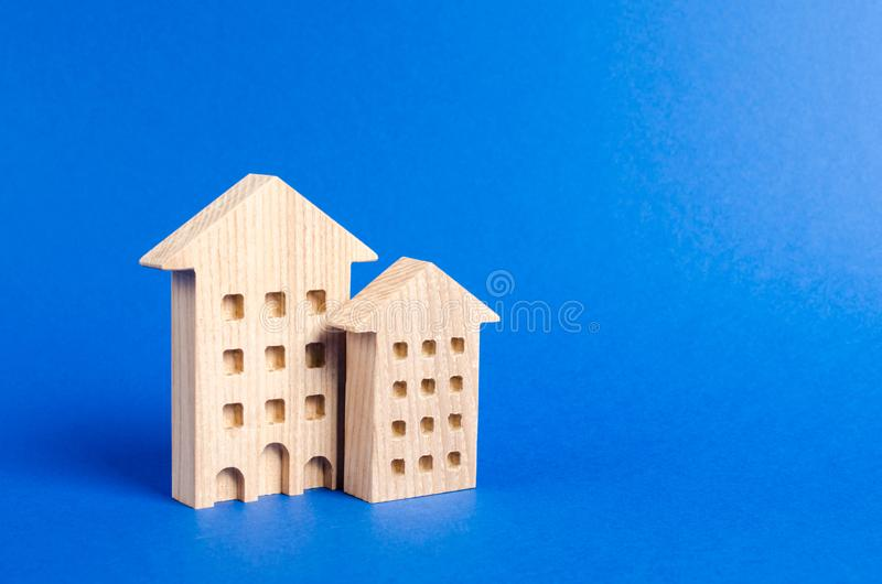 Two residential buildings stands on a blue background. The concept of buying and selling real estate, renting. Search for a Apartment house. Affordable housing stock photos