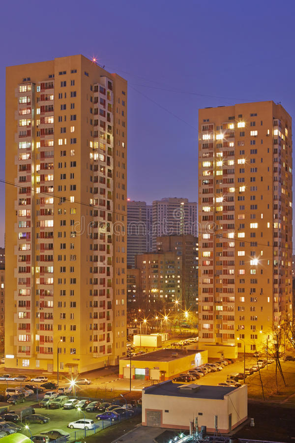 Two residential skyscrapers and adjacent area. With parkings in evening stock images