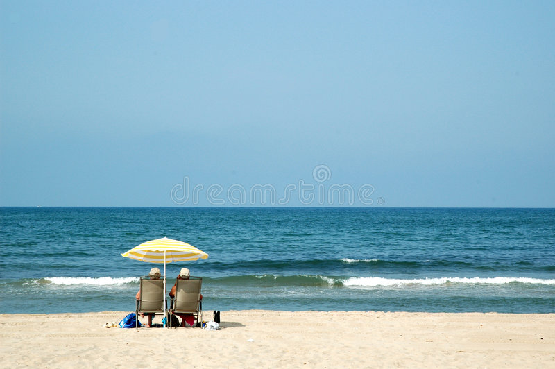Two retired people at the beach. Two retired people are relaxing on the beach royalty free stock image