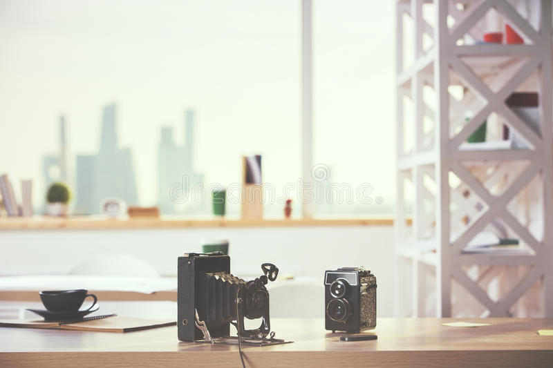 Two retro cameras. Close up of two retro cameras on modern wooden desktop with coffee cup and other items. Blurry city view in the background royalty free stock photography