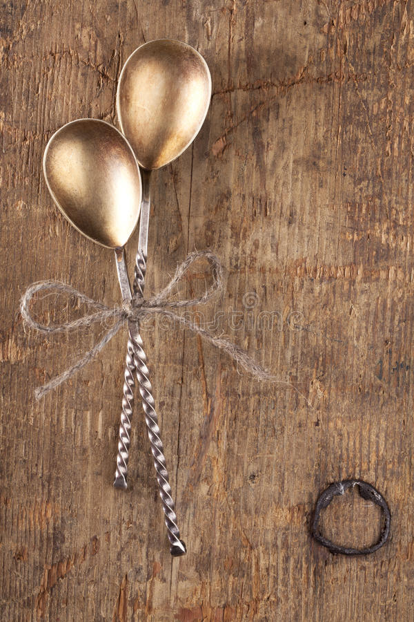 Two retro desset spoons tied on old wooden table.  royalty free stock images