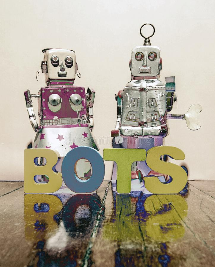 Two retro robot toys and the word BOTS solarized stock photography