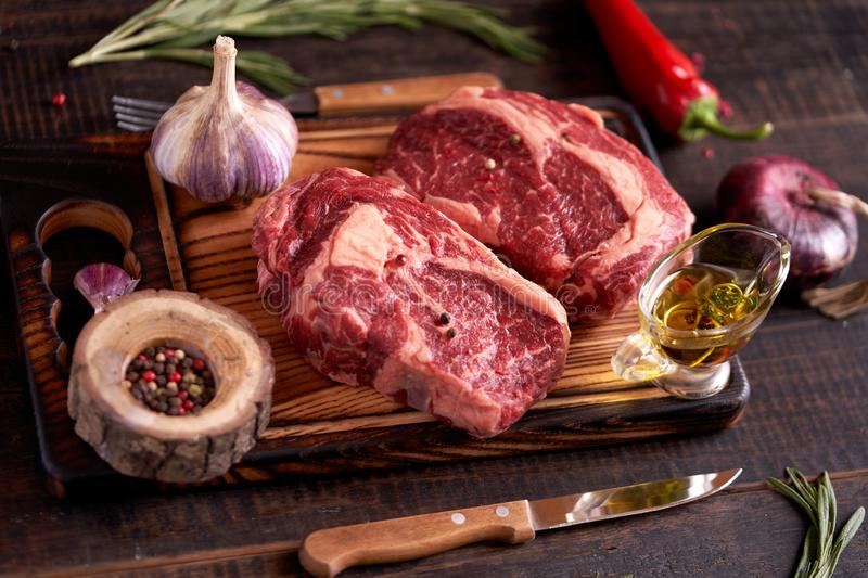 Two rib eye steaks on a cutting board with peppercorns, rosemary, olive oil, red chili peppers, onions and garlic royalty free stock photos