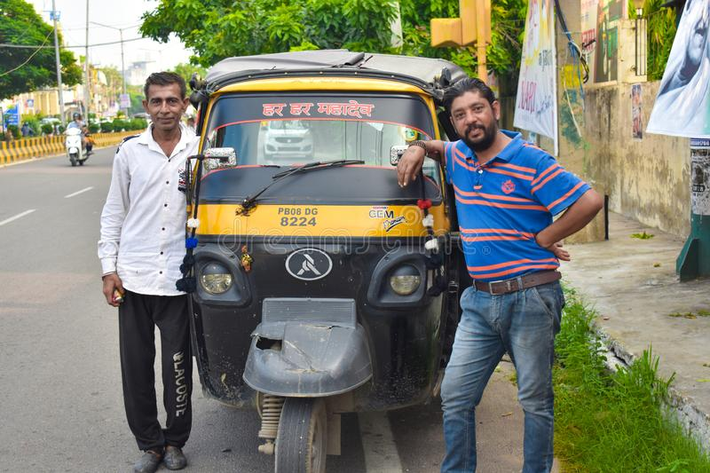 Two rickshaw driver smile with their auto. In Punjab, India stock photo