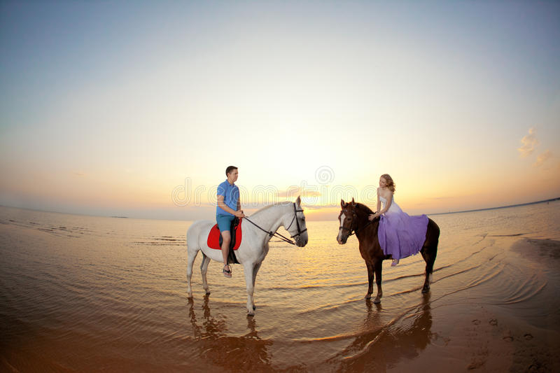 Two riders on horseback at sunset on the beach. Lovers ride horseback. Young beautiful man and woman with a horses at the sea. royalty free stock photos