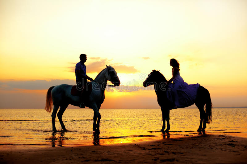 Two riders on horseback at sunset on the beach. Lovers ride horseback. Young beautiful man and woman with a horse at the sea. Rom royalty free stock photos
