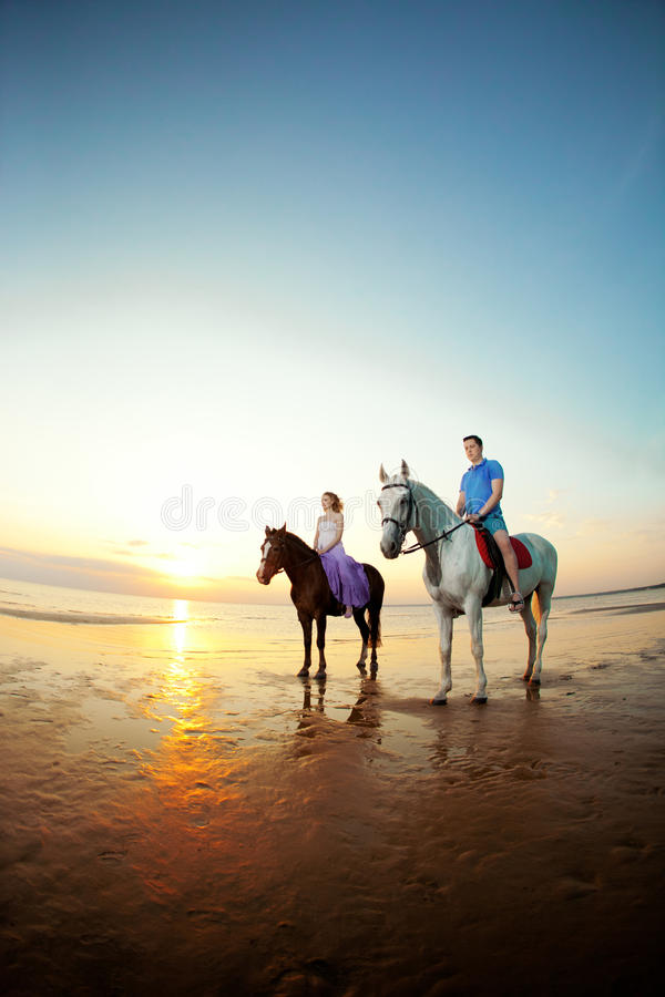 Two riders on horseback at sunset on the beach. Lovers ride horseback. Young beautiful man and woman with a horse at the sea. Rom stock photos