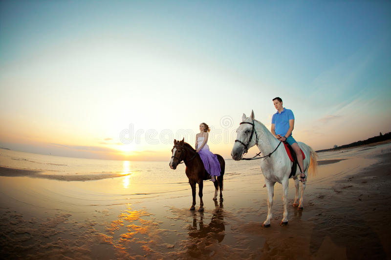 Two riders on horseback at sunset on the beach. Lovers ride horseback. Young beautiful man and woman with a horse at the sea. Rom royalty free stock photography