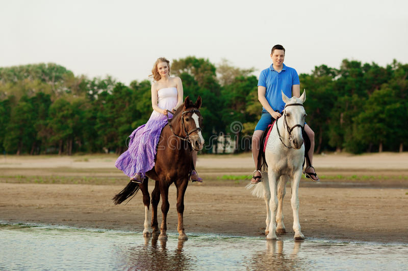 Two riders on horseback at sunset on the beach. Lovers ride horseback. Young beautiful man and woman with a horses at the sea. royalty free stock images