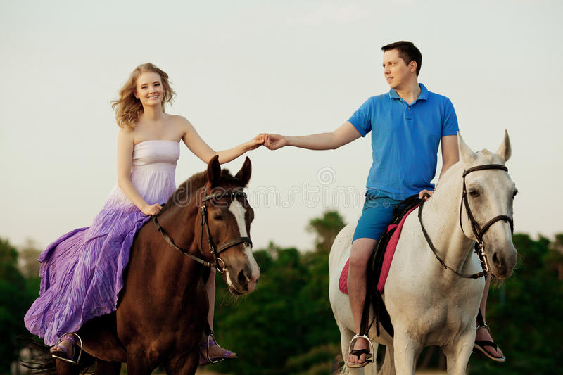 Two riders on horseback at sunset on the beach. Lovers ride horseback. Young beautiful man and woman with a horse at the sea. Rom stock image