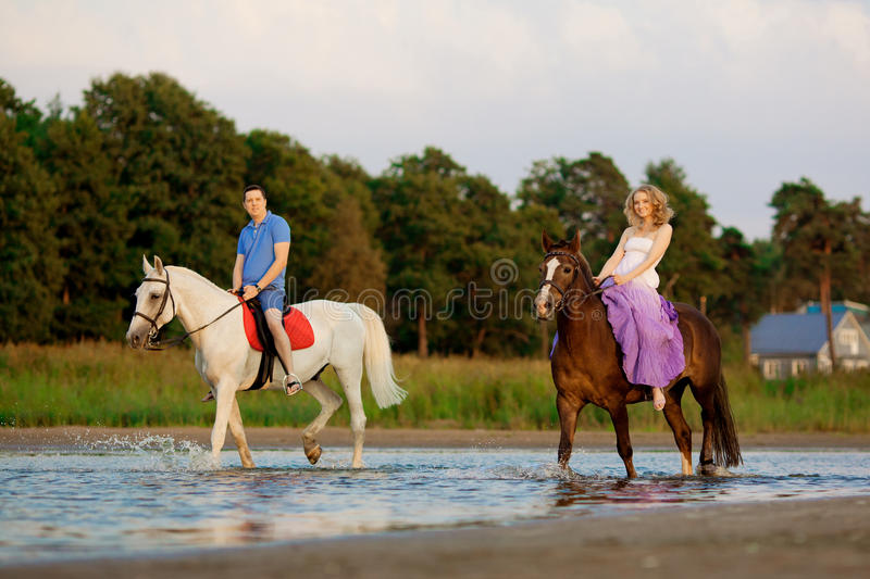 Two riders on horseback at sunset on the beach. Lovers ride horseback. Young beautiful man and woman with a horse at the sea. Rom royalty free stock image