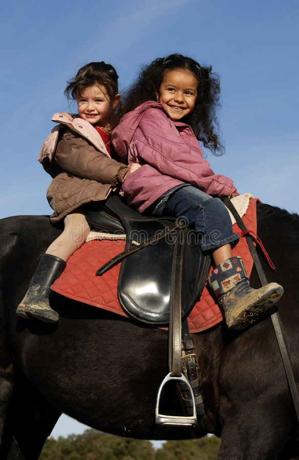 Two riding little girls stock image