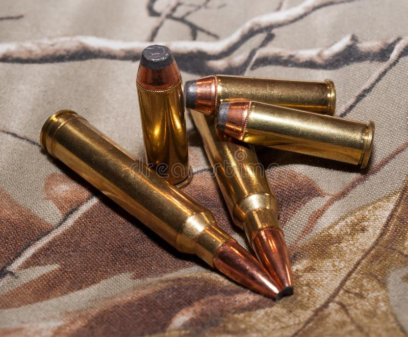 Two different types of bullets, handgun and rifle. Two rifle bullets along with three 44spl bullets on a camouflage background stock images