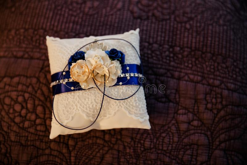 Two ring on white pillow with blue line stock image