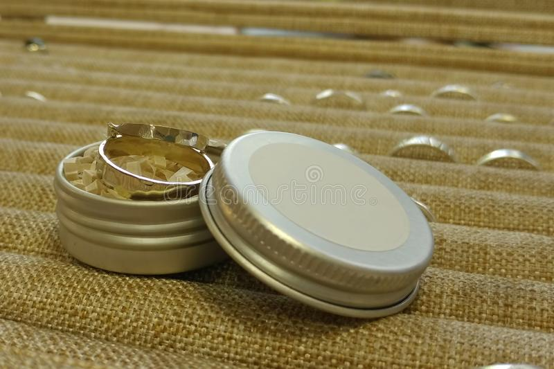 Two rings of white gold are in a round metal box. Against the background of pallets from other jewelry. Wedding diy engagement celebration closeup anniversary royalty free stock image