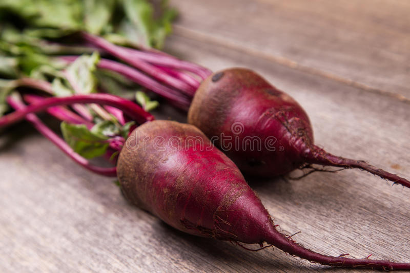 Two ripe beet. Two fresh ripe beet on wooden background in studio royalty free stock photos