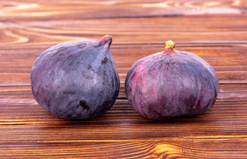 Two ripe figs on brown wooden table stock image