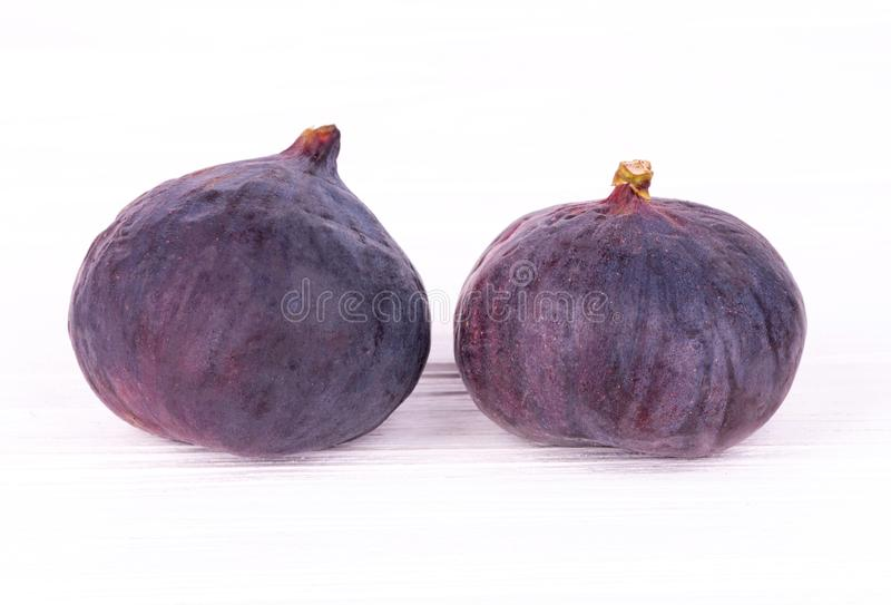 Two ripe figs on white wooden table royalty free stock images