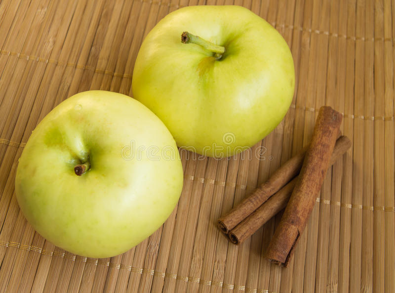Two ripe green apples and cinnamon sticks on bamboo napkin stock image