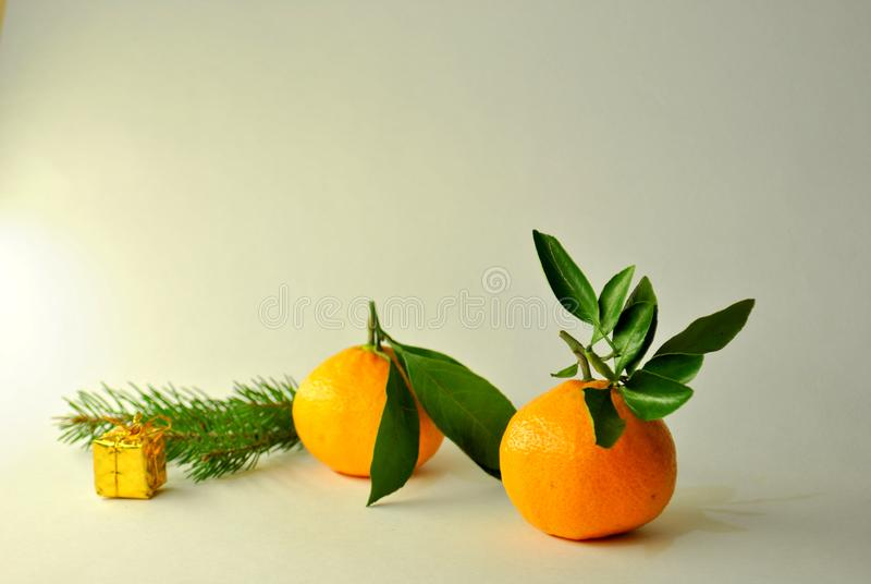 Two ripe juicy tangerines, a branch of spruce and Christmas tree toy on a white background. Two ripe juicy mandarins, a branch of spruce and Christmas tree toy royalty free stock photo
