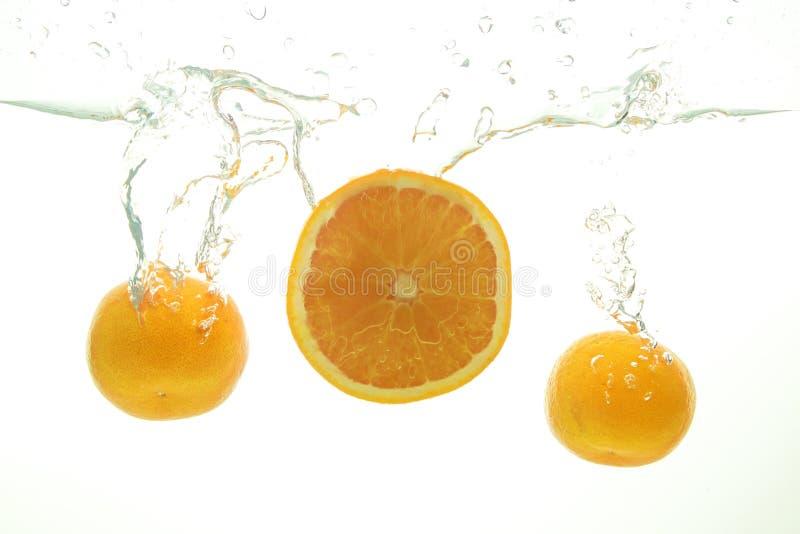 Two ripe mandarine and orange slice splash of water on white. Background stock photos