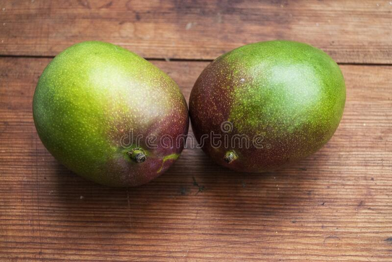 Two ripe mangoes on a wooden background stock photography