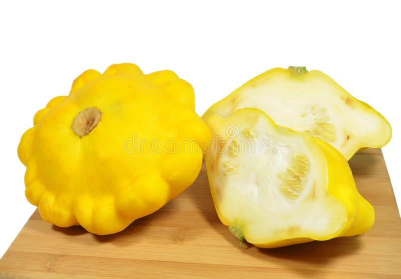 Two ripe yellow squash, one of which is cut into two equal parts lie on a wooden cutting board royalty free stock images