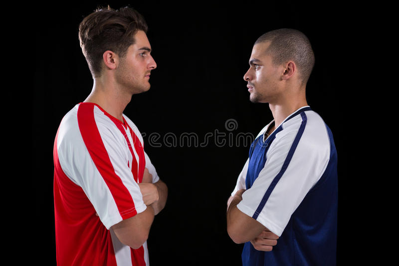 Two rival football player looking at each other. Against white background royalty free stock images