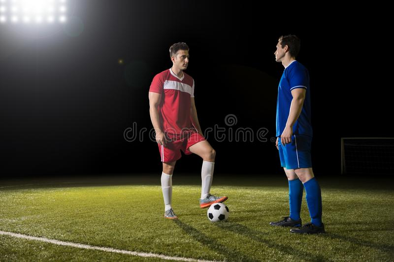 Soccer team opponents playing football. Two rival football player standing on field with ball and looking at each other royalty free stock photography