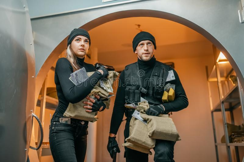 Two robbers with money left the vault. Bank robbery, two robbers with money left the vault. Criminal profession, theft concept, male and female burglars stock photography