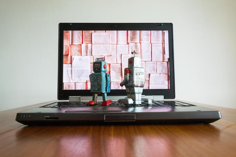 Two robots looking at laptop screen with books, artificial intelligence, big data and deep learning stock photography