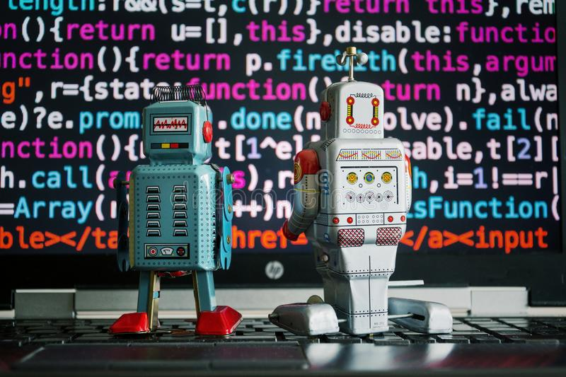 Two robots looking at laptop screen with source code, artificial intelligence, big data and deep learning royalty free stock images