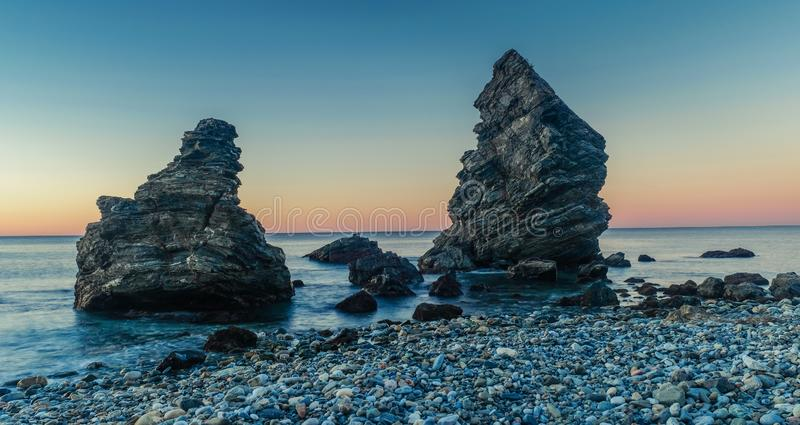 Two rocks in Molino beach, Spain. Nerja, Malaga, Andalusi, Spain - February 4, 2019: Playa del Molino, small stone beach with two large rocks on the shore, Nerja royalty free stock photo