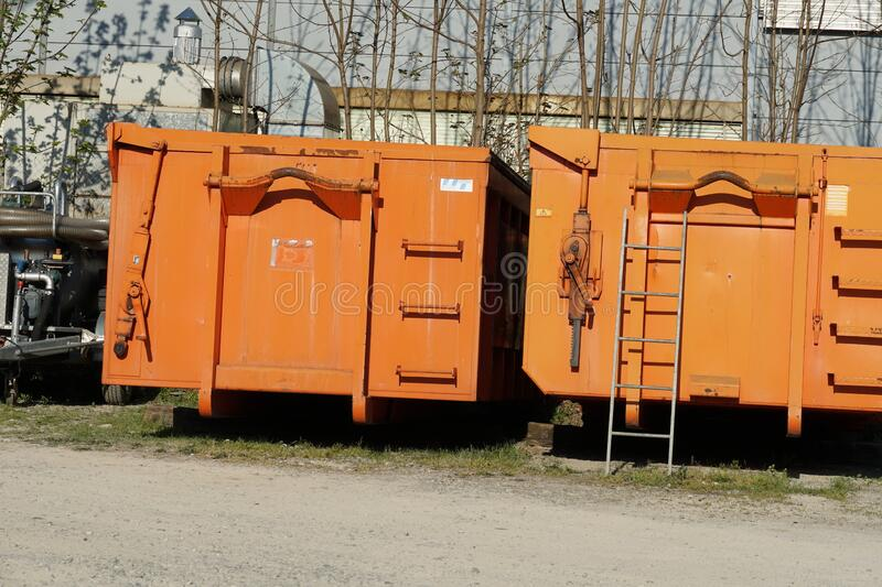 Two roll on/off containers in orange color on one of them is leaned a metal ladder to facilitate access. They are big volume construction waste containers royalty free stock images