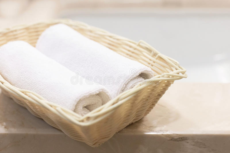 Two rolled white hand towels in rectangular basket stock photo