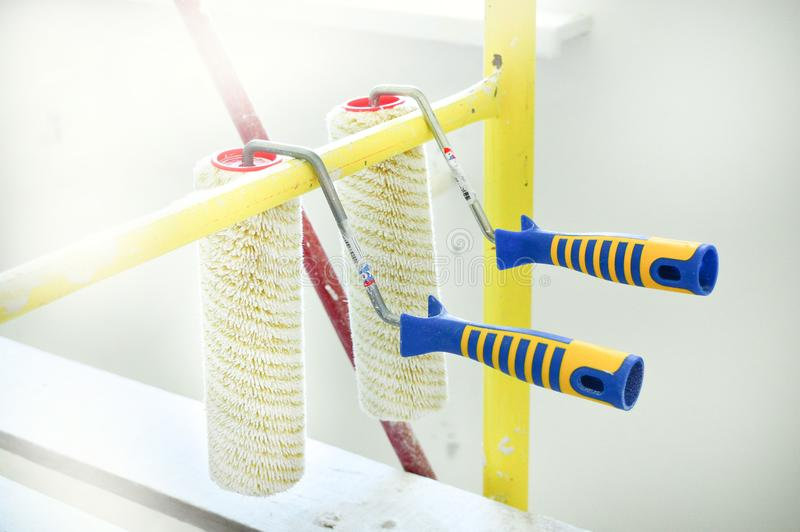 Two rollers for painting walls against the background of the apartment in which the rement is going. The concept of stock images