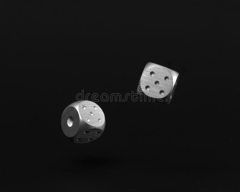 Two Rolling Silver Casino Dice on Black Background showing five and one royalty free stock photography