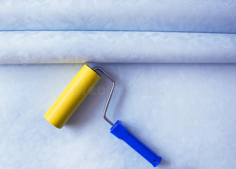 Two rolls of blue Wallpaper and a roller for home repair and renovation royalty free stock photography
