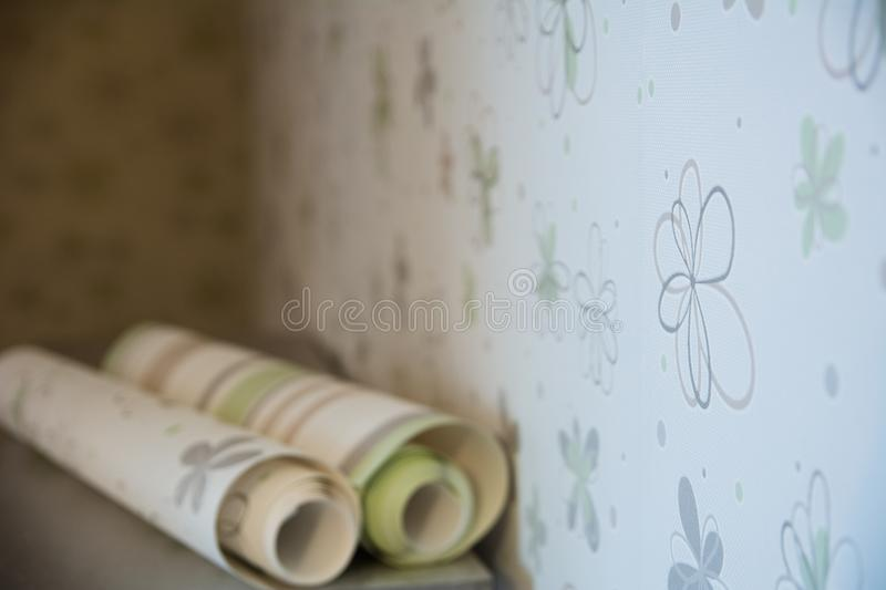 Two rolls of wallpaper lie against royalty free stock images