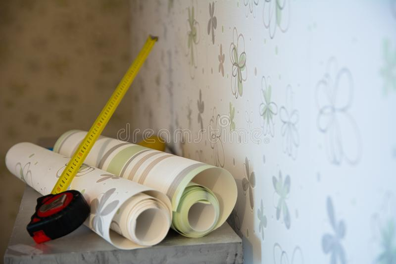 Two rolls of wallpaper and a measuring tape. Measure lie against the wall with floral wallpaper royalty free stock images