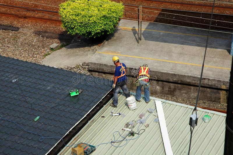 Two roofer construction worker working on tin roof stock photography