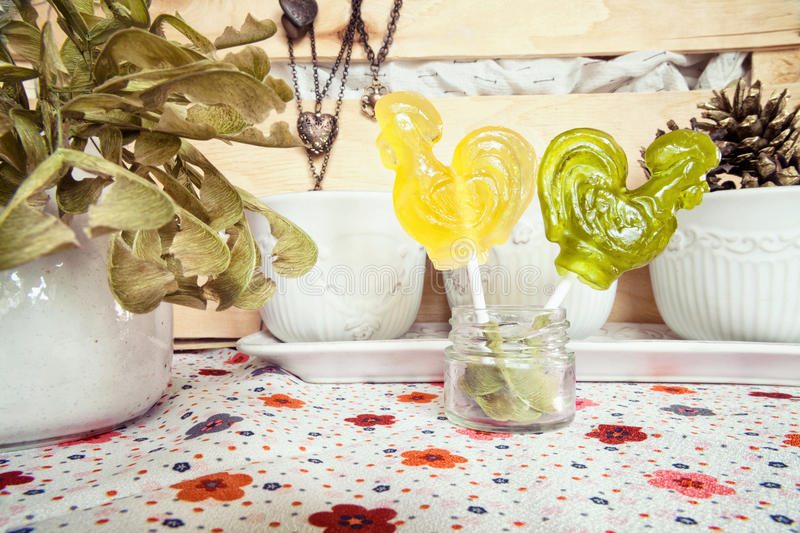 Two rooster shaped colorful lollipops. 2 caramel candies on stick in shape of birds. Arguing couple concept stock photo
