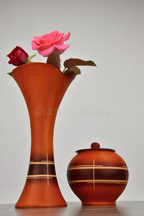 Two Roses In A Ceramic Vase For Flowers The Vase Stands On A Wooden
