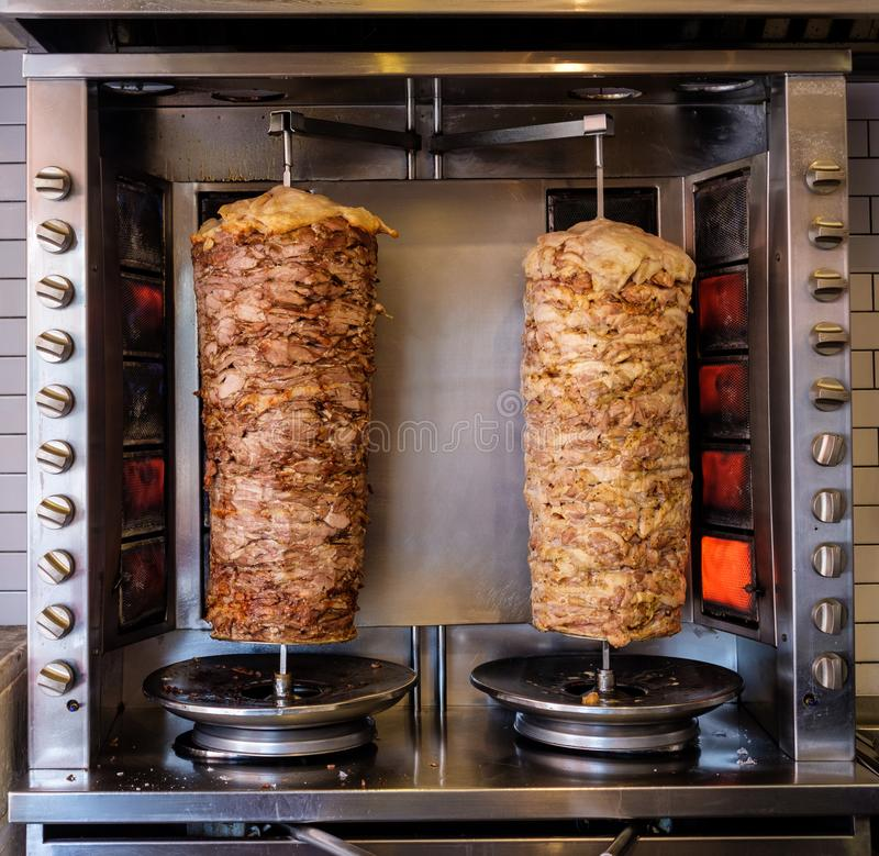 Two rotating skewered chicken and lamb meat grilled in stainless. Steel grill and ready to serve in a typical Middle Eastern fast food kebab sandwich royalty free stock images