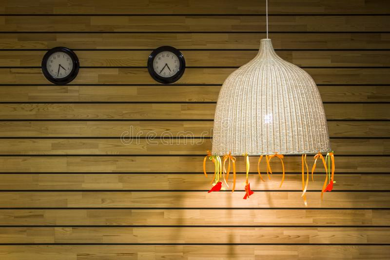 Two round black clocks on the wall of wooden light gray yellow boards with a large wicker lampshade. horizontal lines. natural royalty free stock images