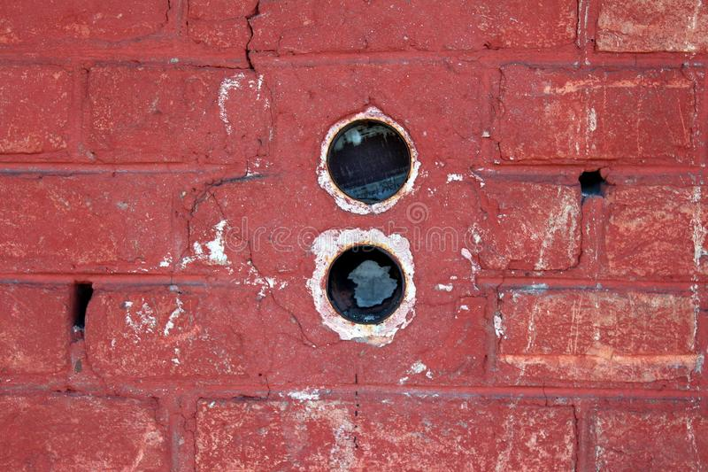 Two round electrical outlet boxes without wires mounted inside dilapidated red brick wall royalty free stock photography