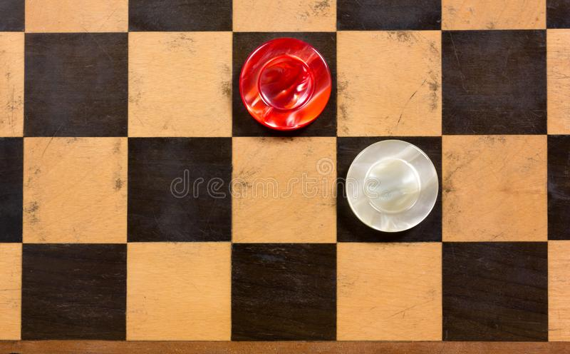 Two Pieces on a Wooden Checkerboard. Two round red and white pearly pieces on an old wooden checkerboard royalty free stock images